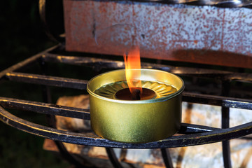 burning candle stands in wrought iron grille grill
