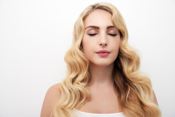 Portrait of beautiful young woman with wavy blond hair and eyes closed standing against white background