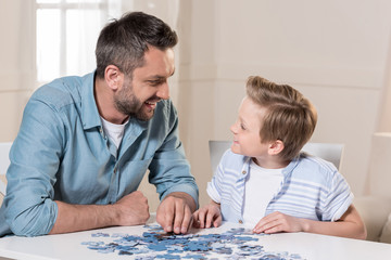 man playing puzzle with son at home