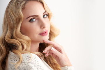Portrait of gorgeous young woman with wavy blond hair posing elegantly looking at camera