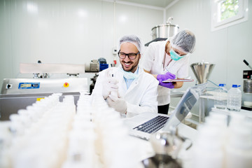 Young technologist making face care creams. Sitting in a cosmetic products factory with his female assistant.
