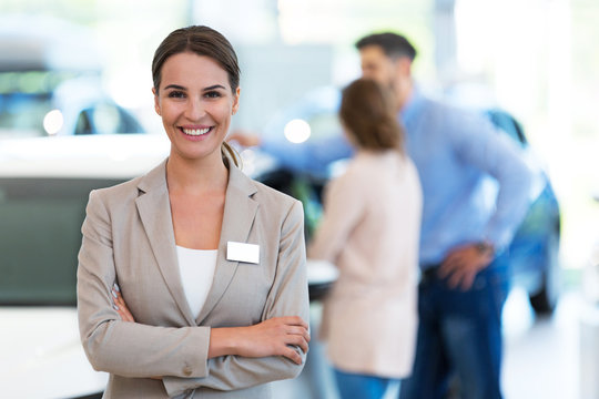 Confident young car dealer standing in showroom