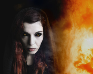 Intense portrait of a witch, fire in background.