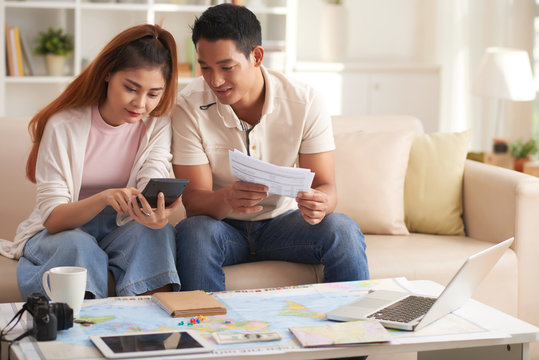 Portrait of young modern couple planning finances for summer vacation