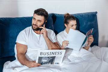 Portrait of young loving couple reading in bed