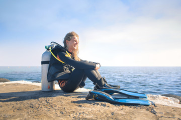 Scuba diver sitting on a pier at the suset
