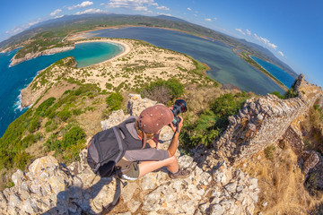 Travel female photographer takes shot of scenic Voidokilia Beach from Navarino Castle ruin in Pylos, Peloponnese, Greece after hiking.Hiker woman photographing a popular greek landmarks. Fish eye view