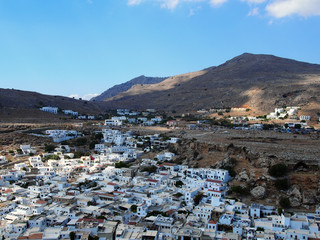 view of the town of lindos in rhodes from above with surrounding mountains