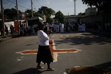 A woman takes pictures of a cross draw on the road at a station of a Corpus Christi procession in Port-au-Prince, Haiti