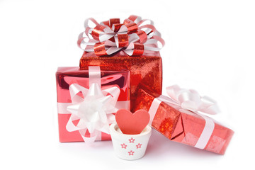 Red gift box with ribbon bow and heart in vase on white background.