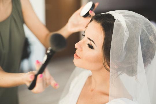 Makeup artist preparing bride to the wedding