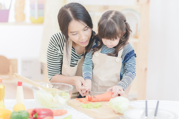 Happy loving family asian mother and her daughter prepare healthy food salad in kitchen room.Photo design for family, kids and happy people concept