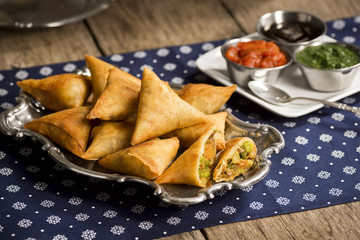 Indian Vegetarian Samosas Stuffed with Potatoes, Peas, Onions, and Carrots, with Dipping Sauces
