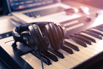 Black headphone on home Music studio keyboard