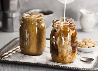 Milk Pouring Into Iced Coffee in Glass Mason Jar