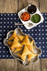 Fried Indian Samosas with Three Dipping Sauces on Table