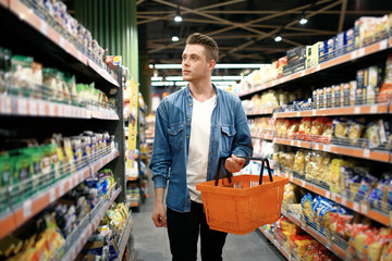 a young man chooses foods at the supermarket