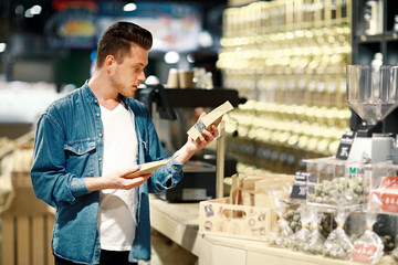 A young man chooses tea in a shop