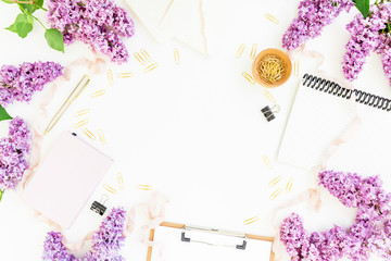 Workspace with clipboard, notebook, envelope, lilac and accessories on white background. Flat lay, top view. Beauty blog concept.