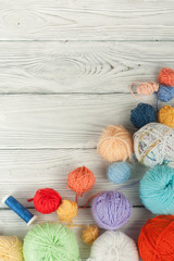Colored yarn on a white background. Skeins of wool yarn for knitting. Balls of wool of different colours for handmade knitting on a wooden background with copy space for ad.
