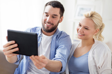 smiling happy couple with tablet pc at home