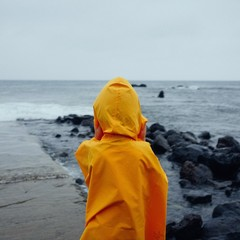 Rear View Of Boy In Yellow Raincoat Standing On Beach