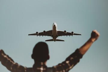 Rear View Of Man With Arms Outstretched Against Airplane Flying In Sky
