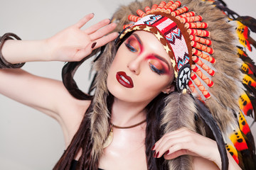 Indian woman with traditional make up and headdress looking to the side. Red Indian woman with a roach on her head