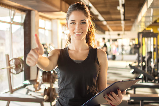 Portrait of personal trainer with clipboard showing thumb up at gym.