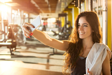 Young sporty woman taking a selfie with mobile phone for social networks at gym.