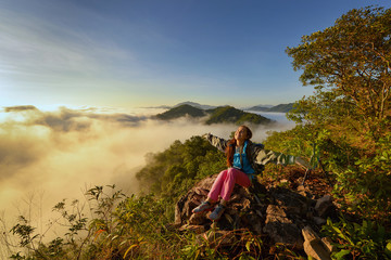 cheering woman hiker open arms at mountain peak,Young girl spreading hands with joy and inspiration facing the sun,Girl enjoying the freedom in mountian mist on sunrise,sunrise effact and mist