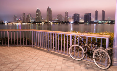A bike is locked to the fence in Coronado with San Diego in the background at night