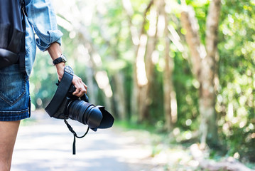 Professional woman photographer taking outdoor portraits with prime lens. Greenery tone 2017