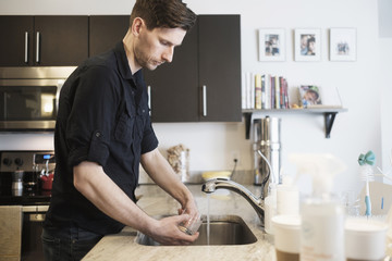 Man washing drinking glass in kitchen