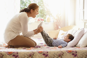 Mother playing with son (2-3) on bed