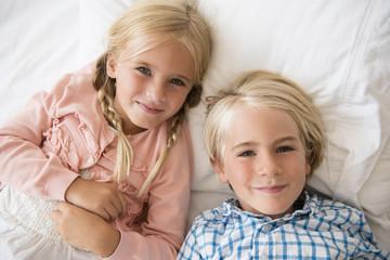 Boy (4-5) and girl (6-7) looking at camera