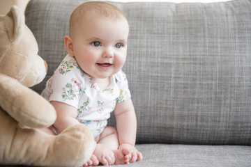 Baby girl (12-17 months) with teddy bear sitting on sofa