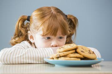 Girl (4 -5) looking on plate of cookies