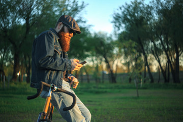 Bearded guy with mobile phone near fix bike. A brutal young man with a huge beard in sunglasses and a cap in the woods at sunset. Lifestyle.