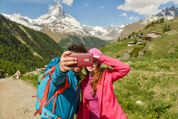 A couple hikers Hiking with backpacks walk along a beautiful mountain area. Taking a selfie. Holding the phone. The concept of active rest. Switzerland 2017