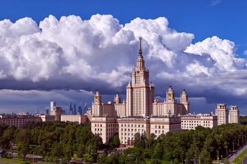 A landscape view of rainy clouds over the sunny spring campus of Lomonosov Moscow State University under blue sky