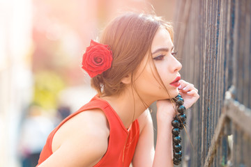 Thoughtful girl with red roses in hair and black beads