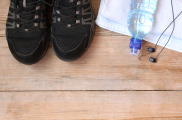 Sport equipment, shoes, water, earphone and towel on wooden background