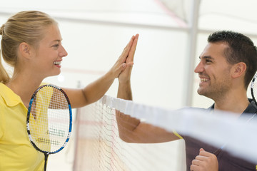 couple doing high five after badminton match