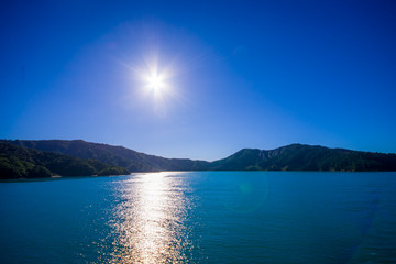 Beautiful landscape with sun shines in the sky with gorgeous blue sky in a sunny day seen from ferry from north island to south island, in New Zealand