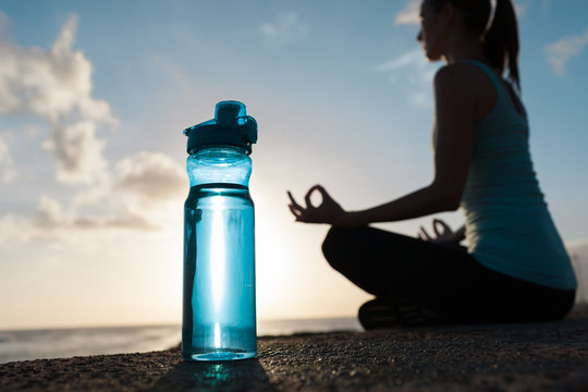 Drinking water and fitness concept. Bottle of water next to woman meditating.
