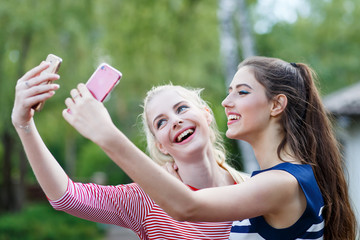 Happy girls making fun and taking selfie