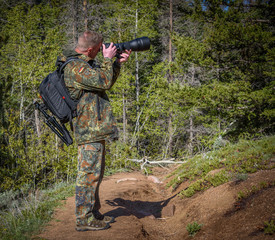 Wildlife, nature man photographer in camouflage outfit with a backpack and tripod standing on a mountain forest trail and shooting, taking pictures