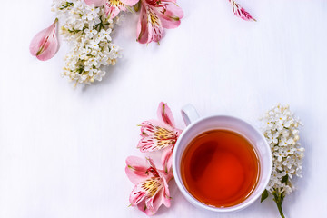 Cup of black tea with a bouquet of lilac on a white table