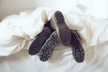 pieds homme femme avec des bottes sous la couette